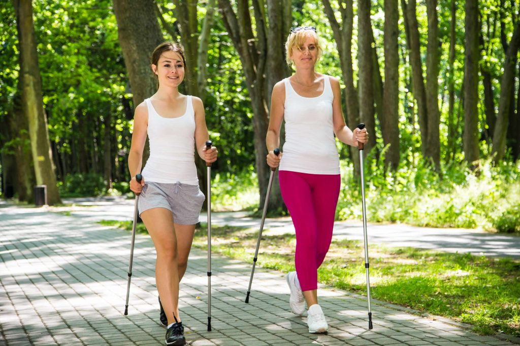 two women Nordic walking in a park