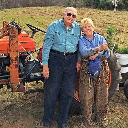 Roger and Sally Conklin standing by a tractor in a farm field