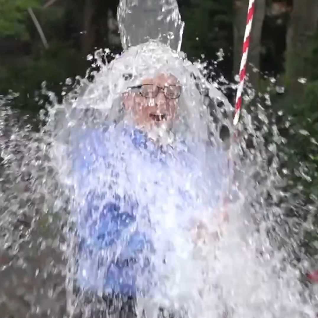 a man in a business suit having ice water dumped on his head for the ALS ice bucket challenge