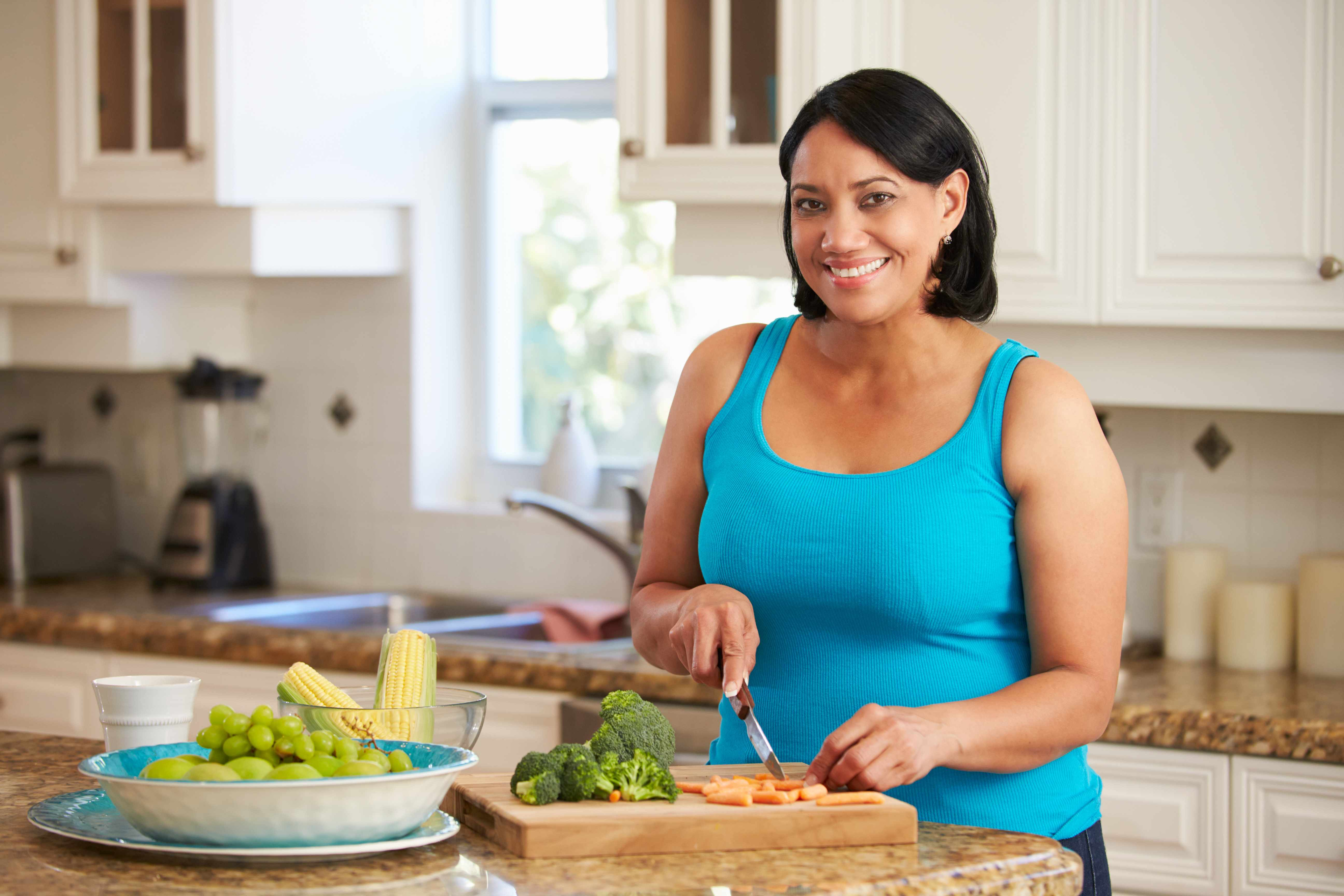 a smiling, overweight middle-aged woman preparing food in a kitchen