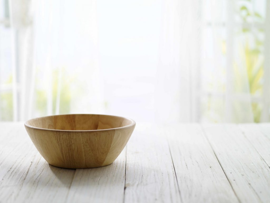 a wooden bowl on a bare table in the bright morning sunlight