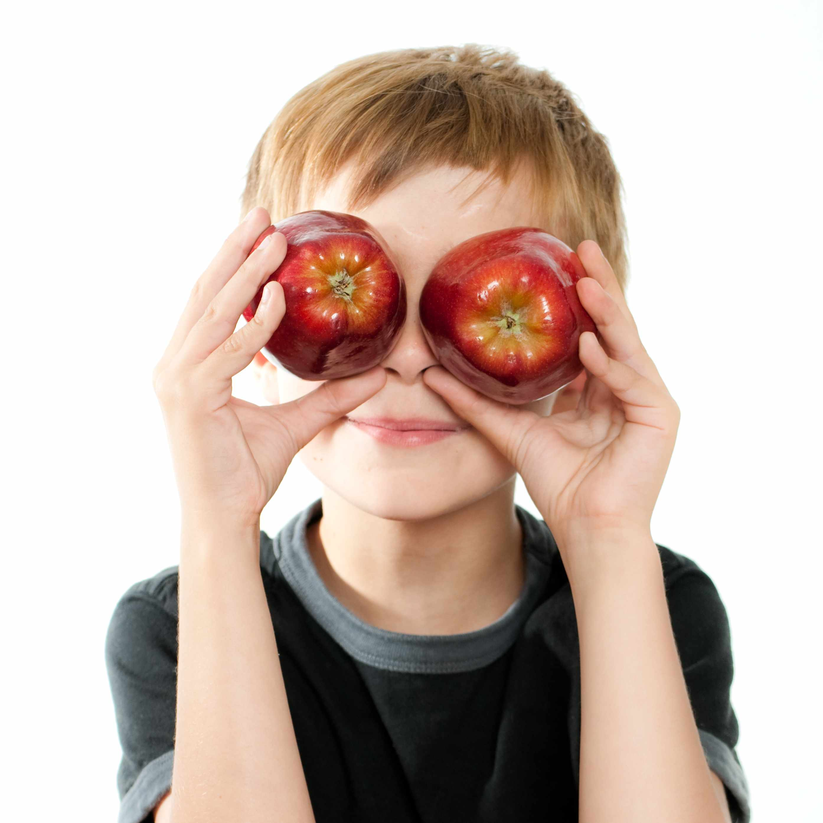 a young boy holding two red apples up in front of his eyes