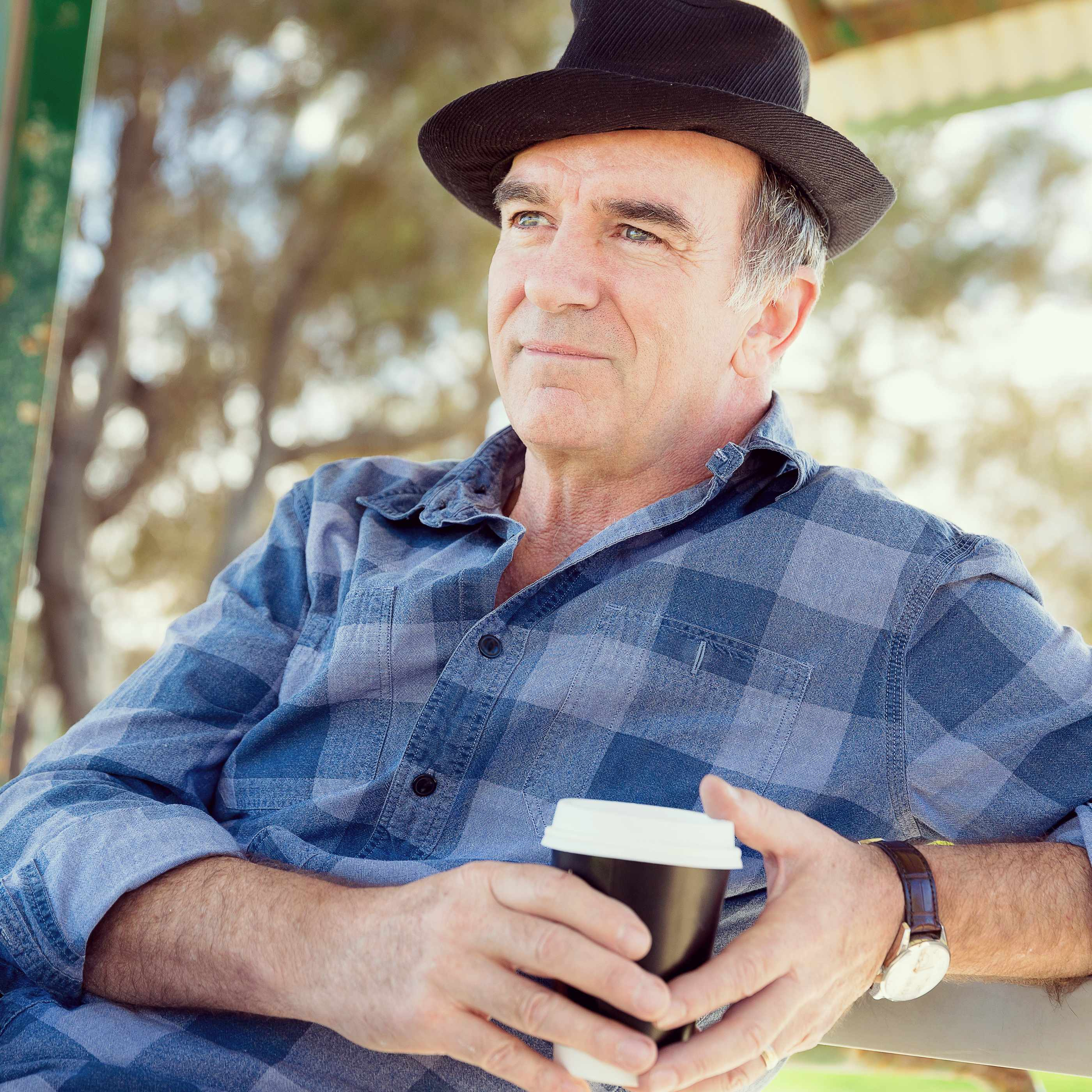 an older man sitting outside with a cup of coffee in his hands and a hat on his head