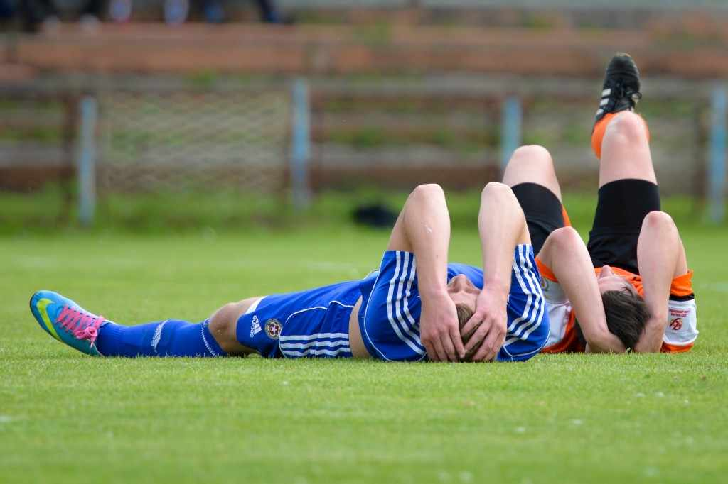 athletes on soccer sports field holding injured heads, perhaps concussions