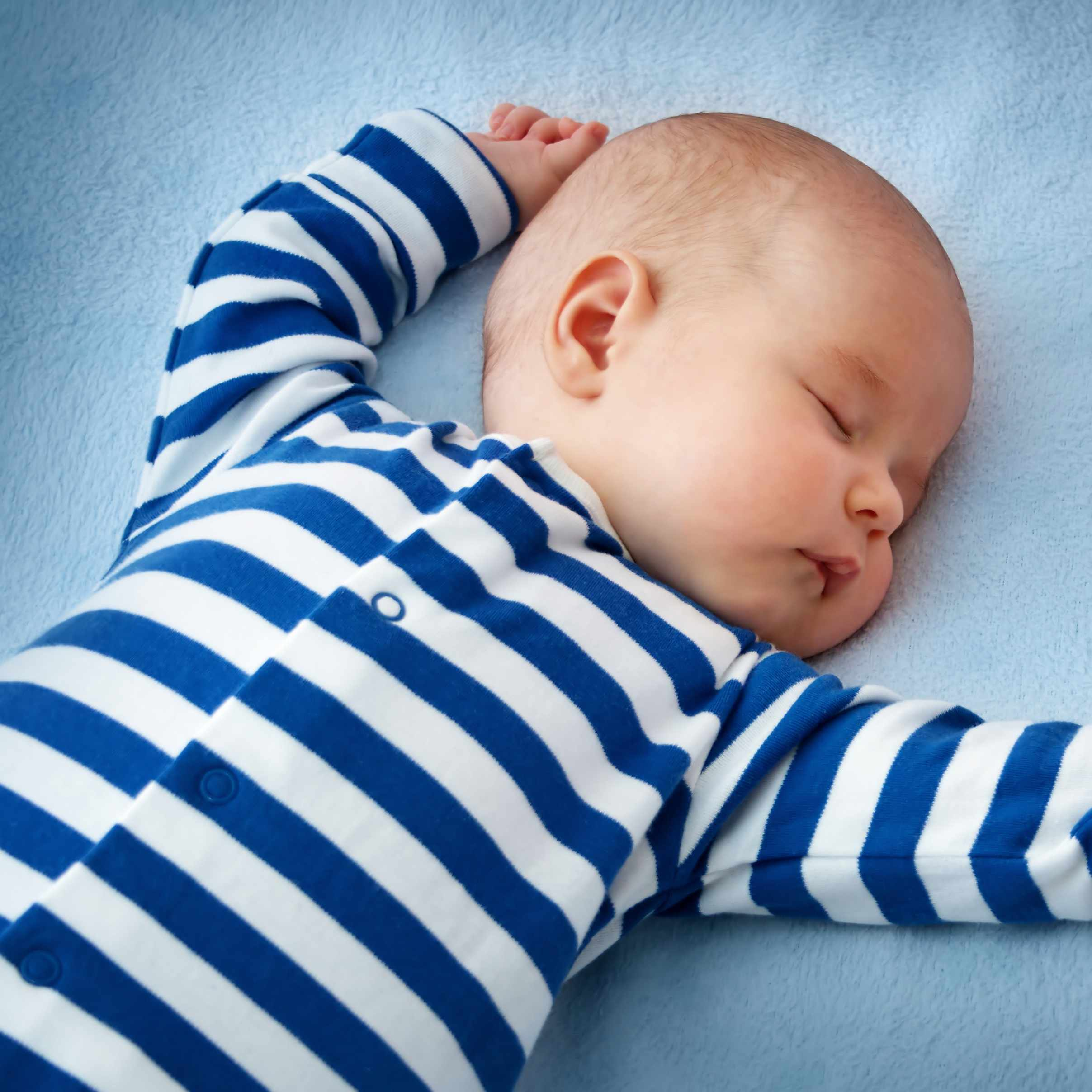 baby sleeping on his back in a crib with blue sheets