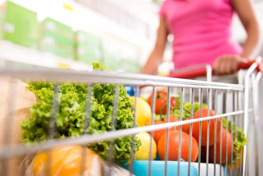 a woman pushing a shopping cart in the store, filled with vegetables for healthy eating