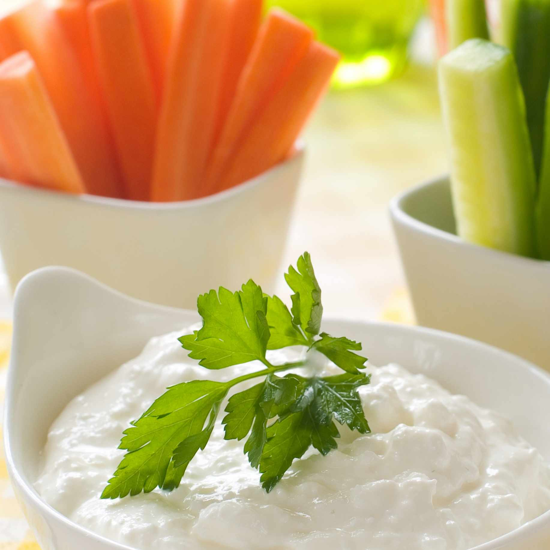 a healthy vegetable snack of carrots and cucumbers with a bowl of dressing dip
