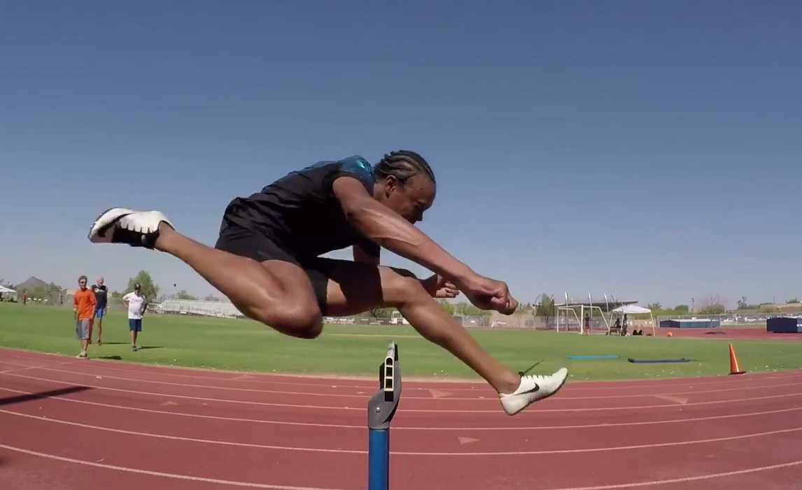 Olympian Aries Merritt jumping a hurdle on a track