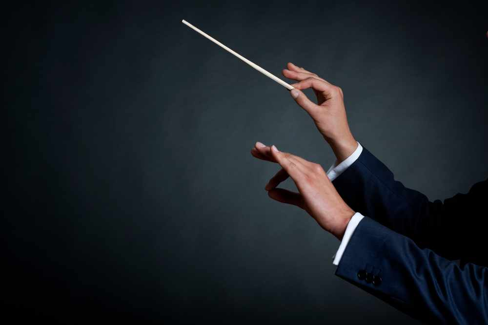 image of a male orchestra conductor directing with his baton in concert