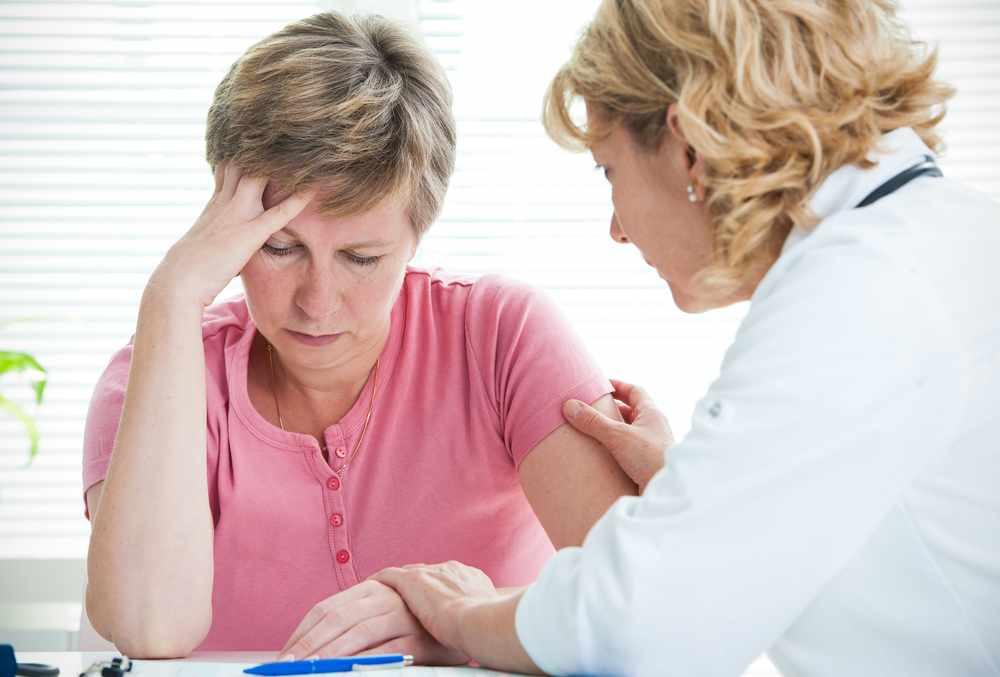 A woman patient receives a cancer diagnosis from the doctor.
