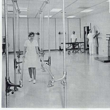 a 1967 photo of Janet Borg, PT aide; Melvin Peterson, orderly; and Edwin Wessner, staff therapist in the gymnasium