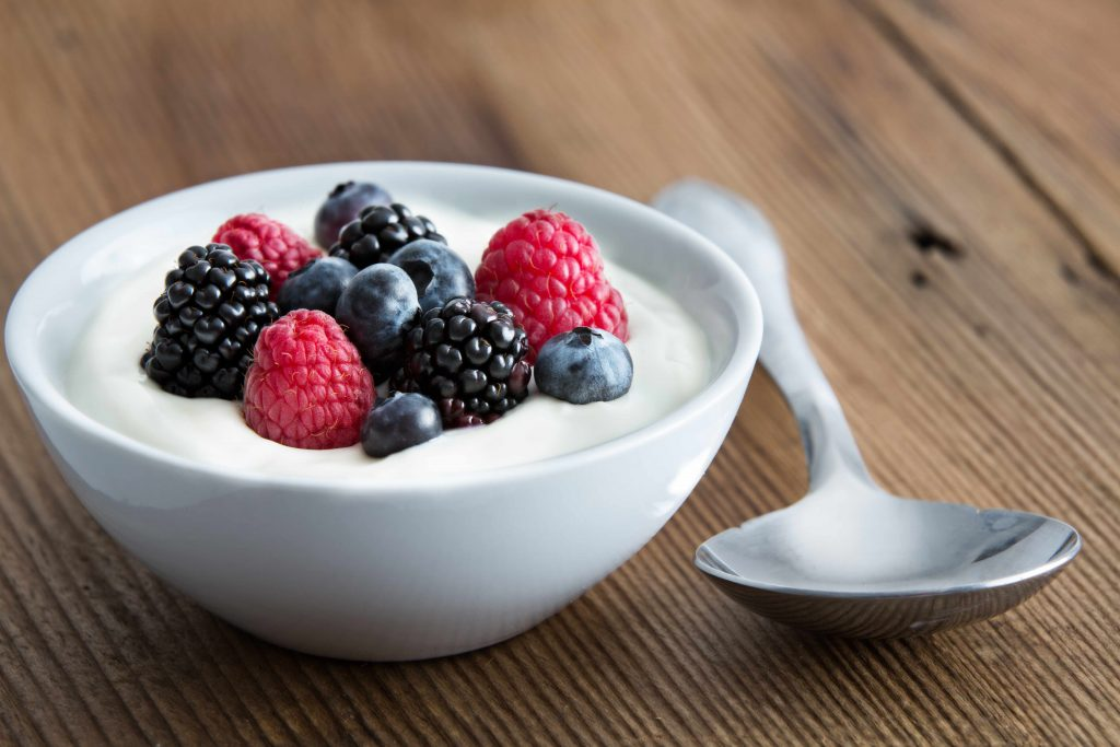 a bowl of yogurt topped with fresh berries, set on a wooden table alongside a large silver spoon