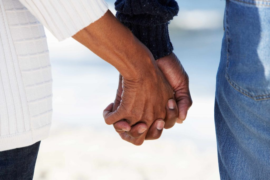 a closeup of a two hands entwined