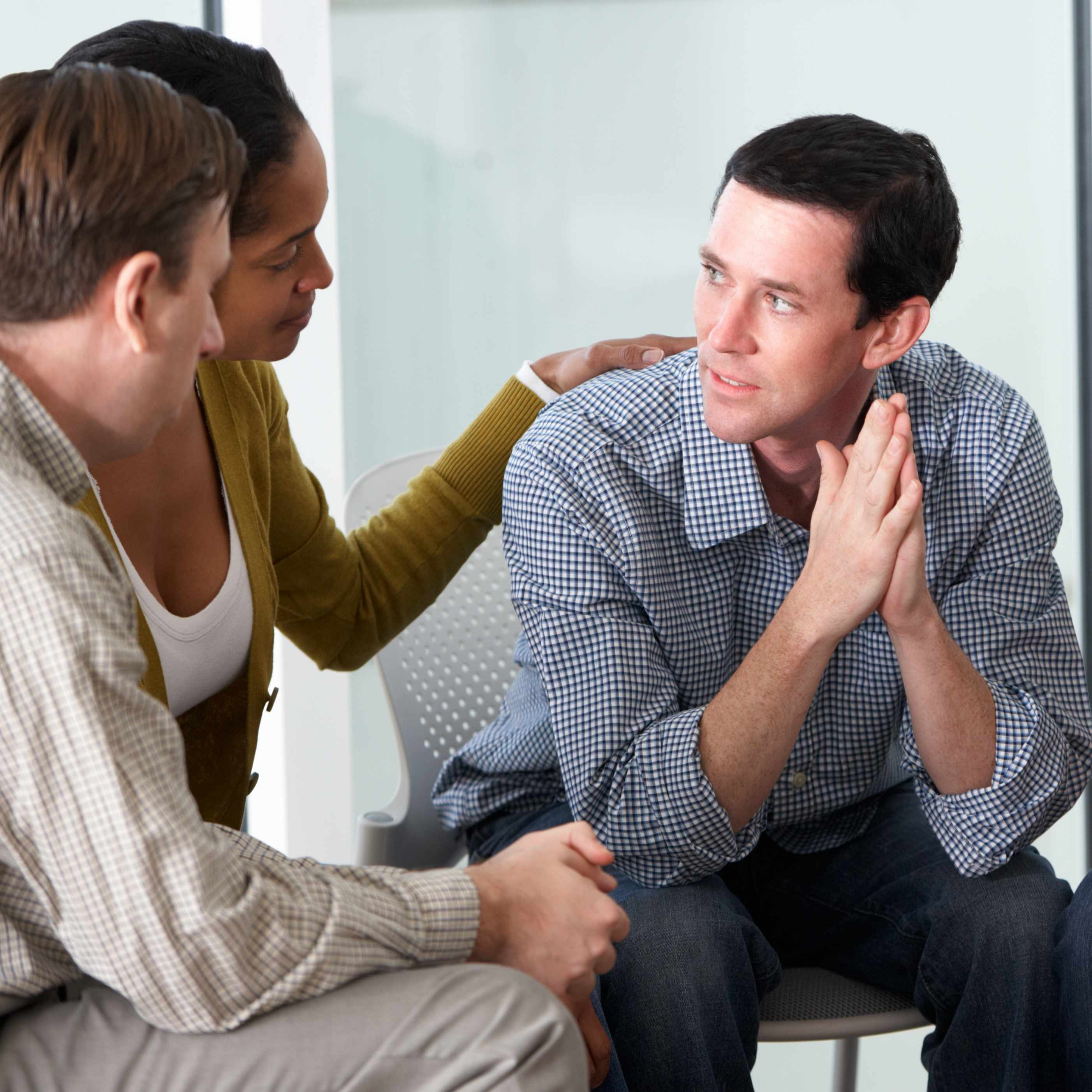 a group of people in a counseling session discussing problems with depression or addiction
