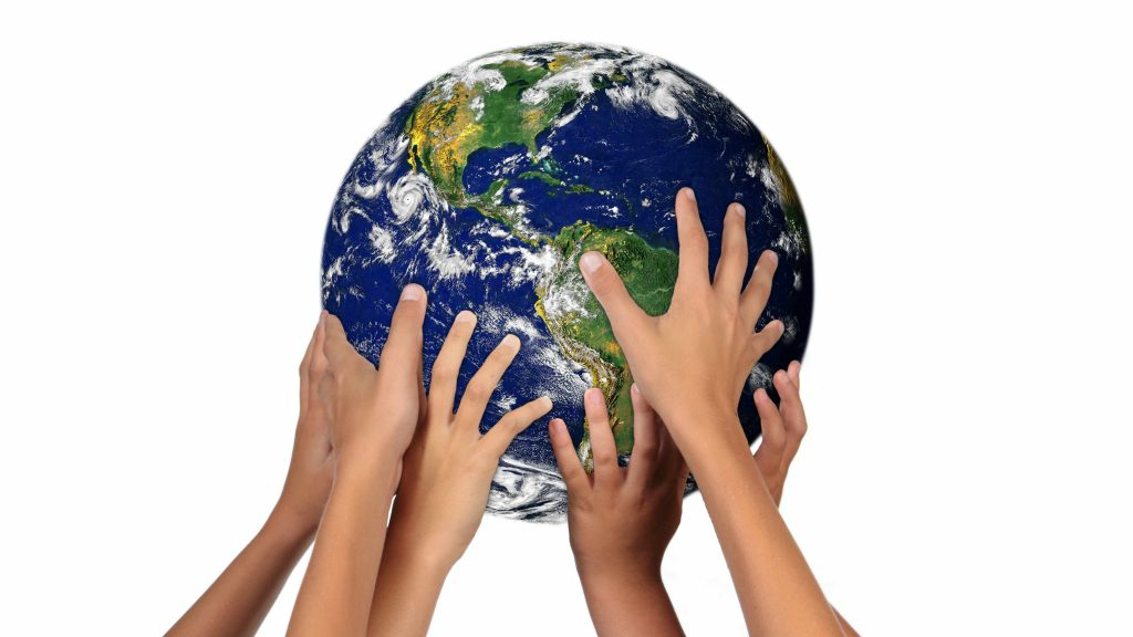 a group of young people's hands holding up the earth, the world, a globe
