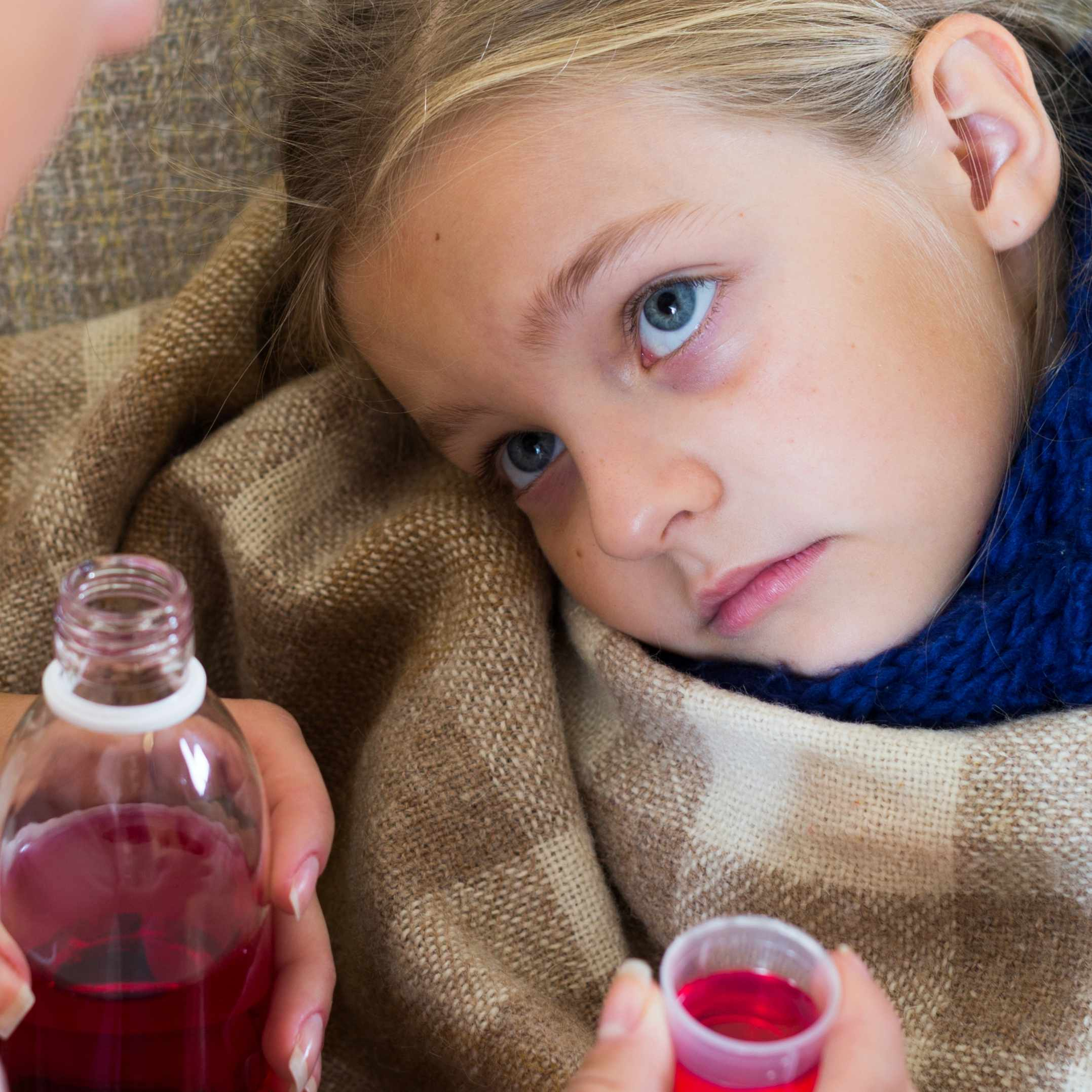 a little girl looking sick and sad with adult trying to give her cough medicine