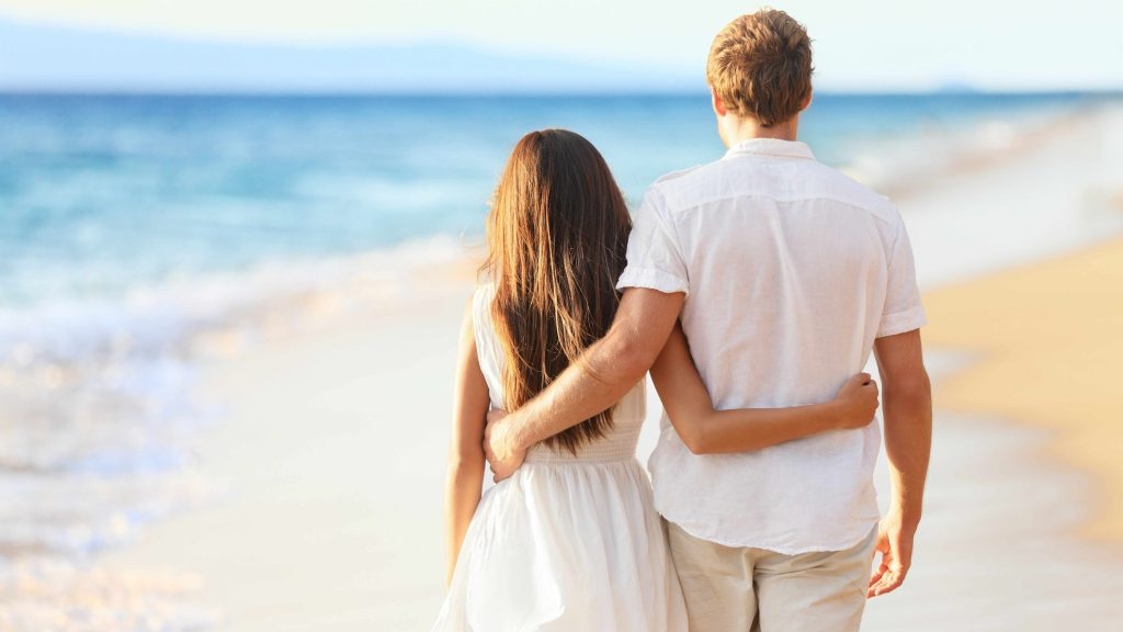 a young couple walking arm and arm along the beach