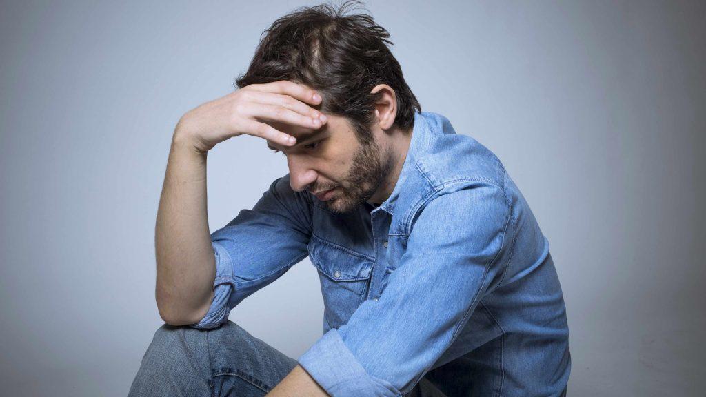 Un joven deprimido se sostiene la cabeza