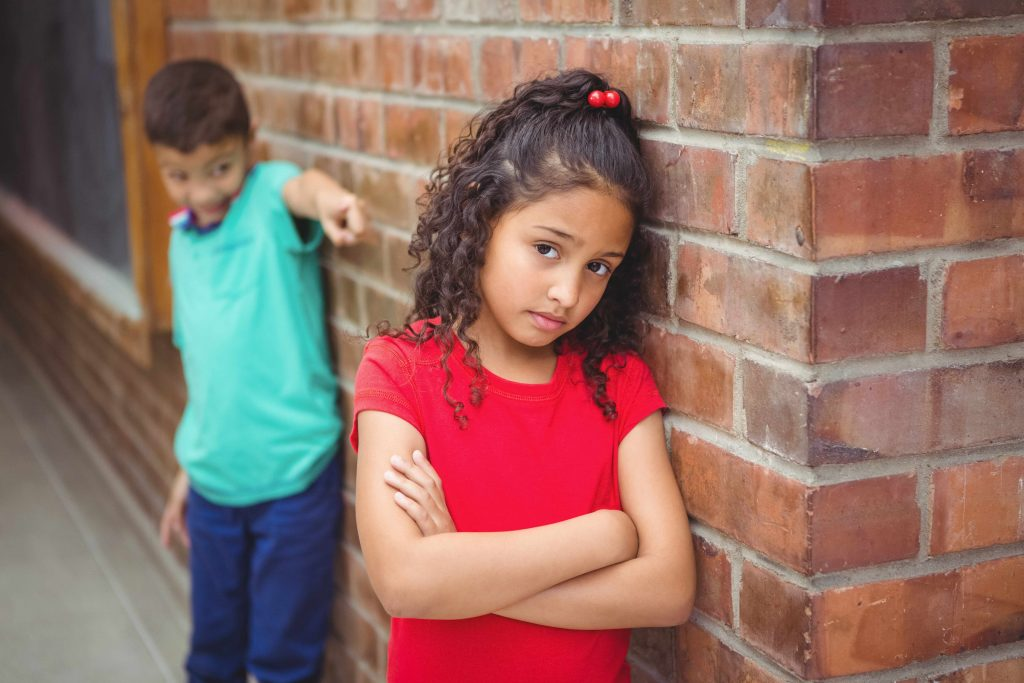 an upset child being teased or bullied by another child at school