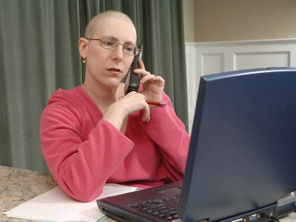 ovarian cancer patient Cindy Weiss on the phone and working at computer
