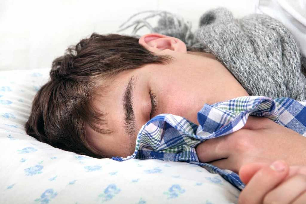 a teenage boy in bed looking sick with flu or cold