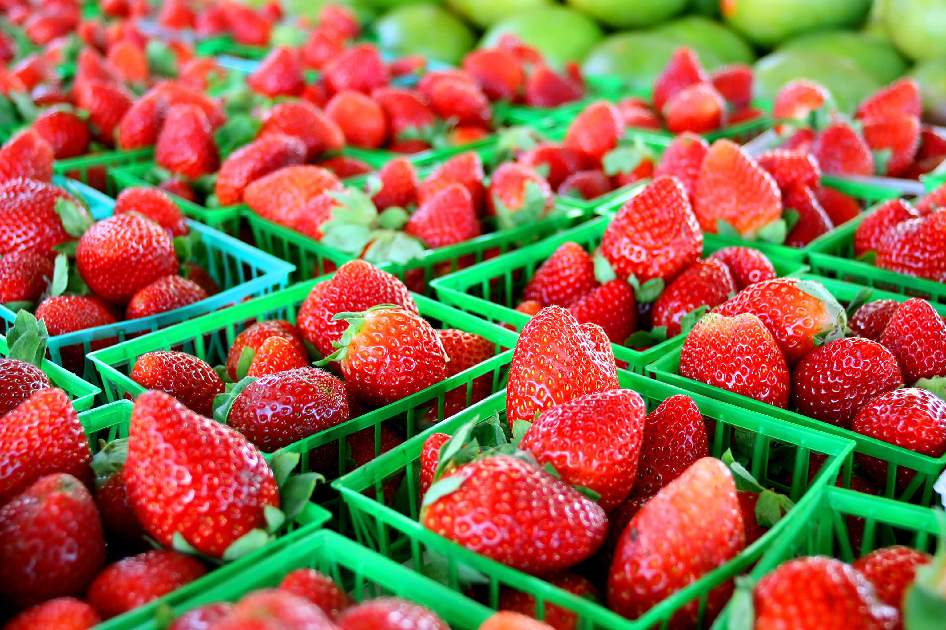 small baskets of strawberries in a fruit market