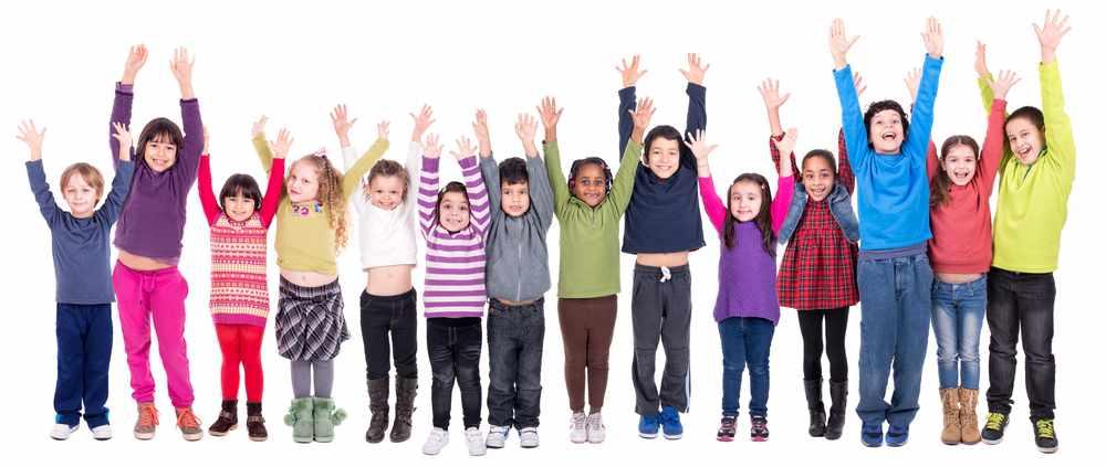 Un grupo de niños en fila sonríen y levantan los brazos al aire