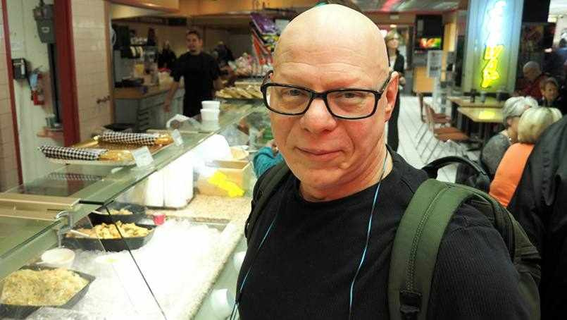 cancer patient Marty Weintraug in a cafeteria wearing a backpack