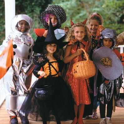 a group of children on a porch, dressed up for Halloween trick-or-treating