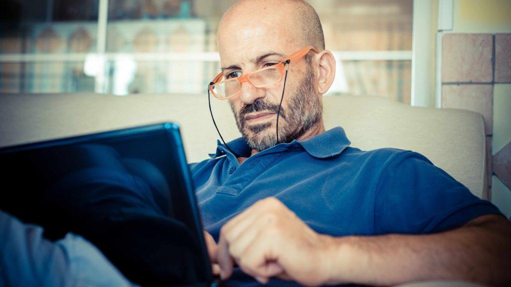 Hombre de mediana edad, calvo, con lentes y sentado en un sofá mientras mira a la pantalla de una computadora portátil