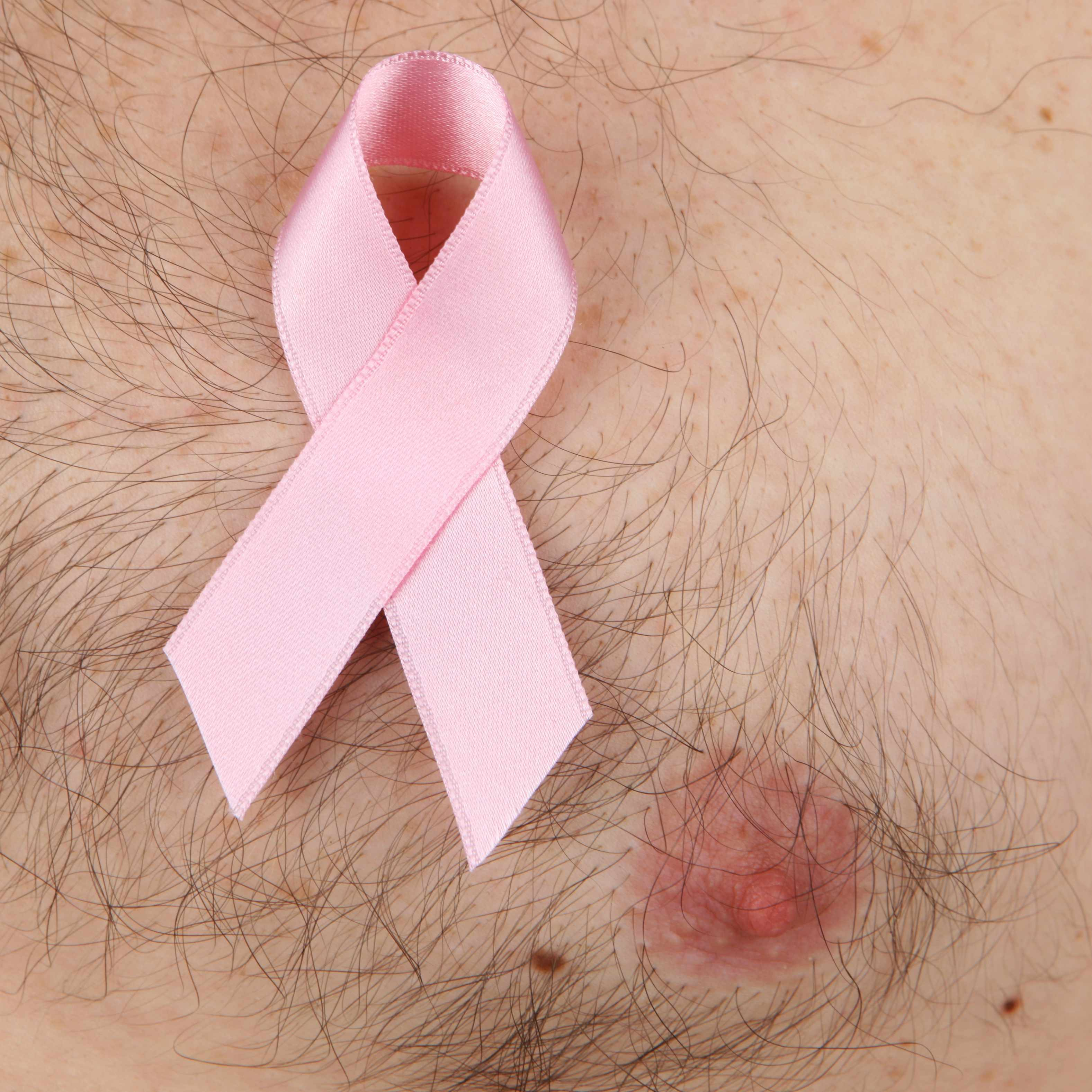 a man's chest with a pink breast cancer ribbon