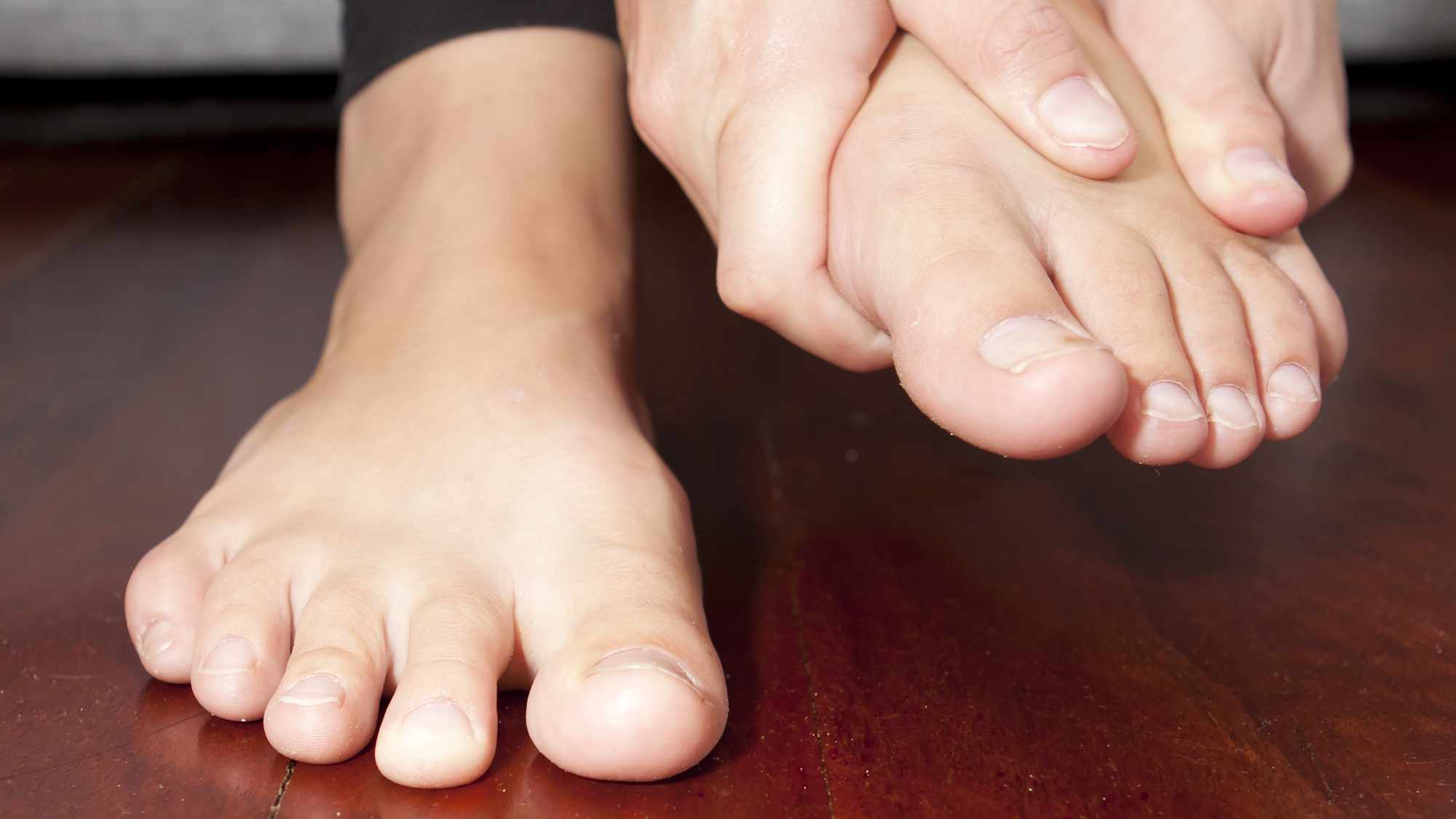a closeup of person barefoot showing toes and two feet, one on the floor and the other held in the person's hands