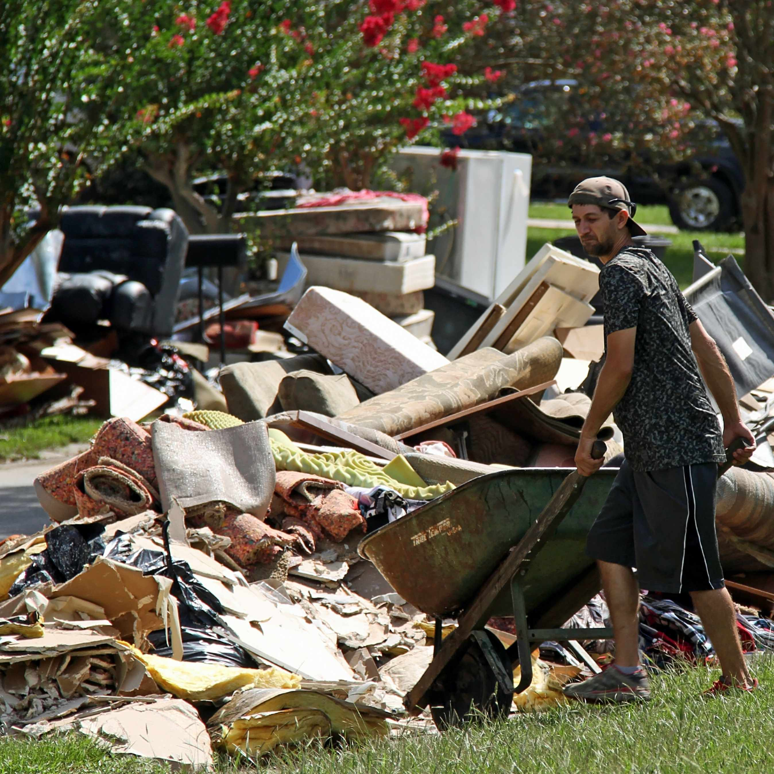a man cleaning up storm debris with wheelbarrow