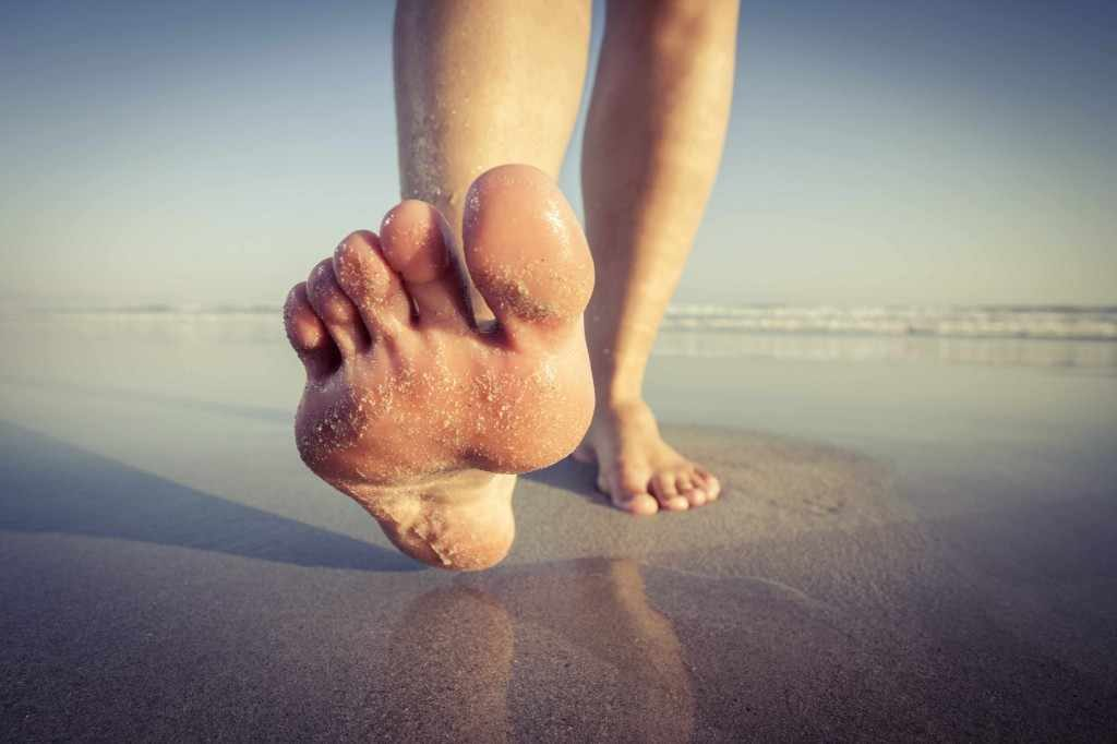 a person's feet walking barefoot on the beach