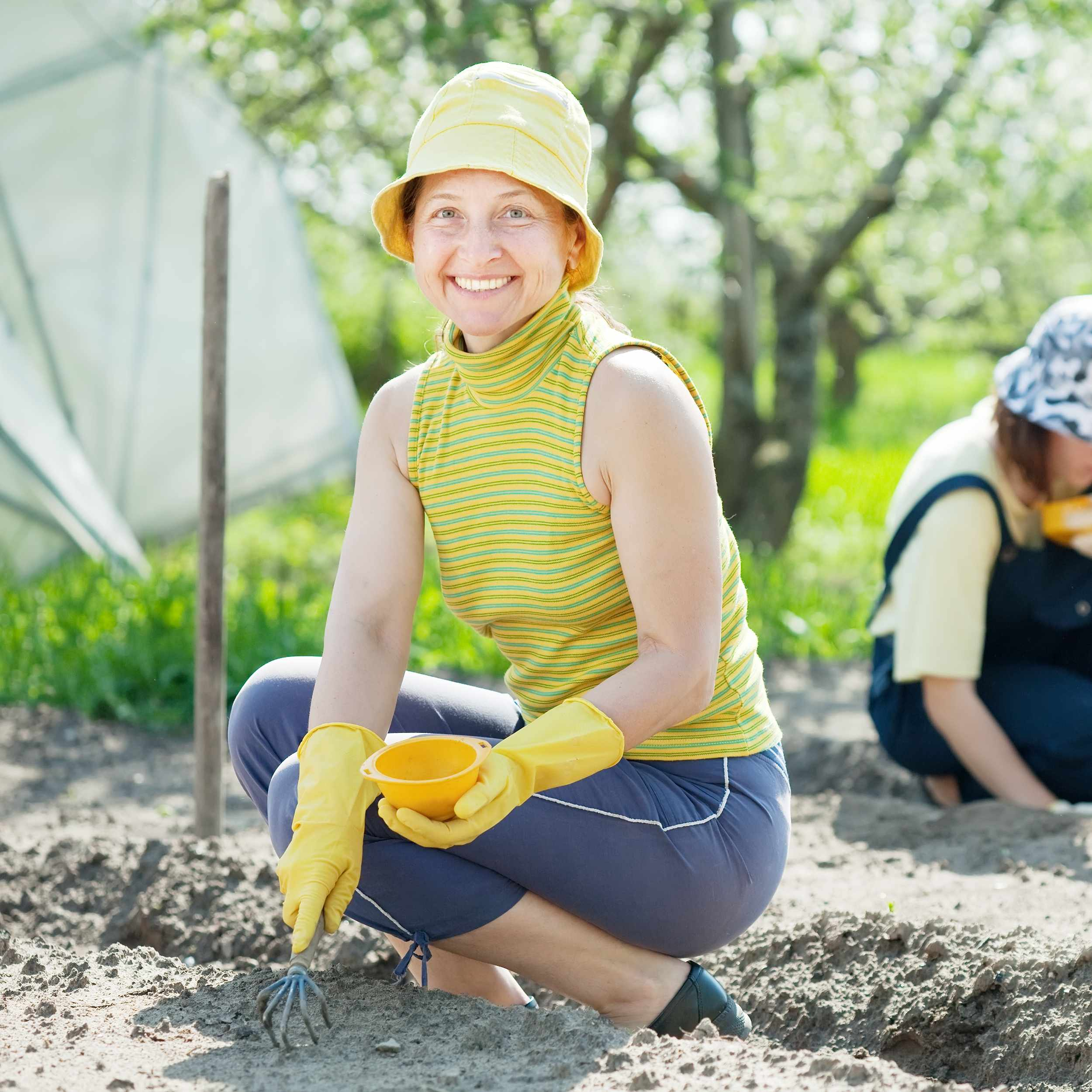 a smiling woman wearing a hat, crouched down, working in a garden, with a younger woman and child in the background