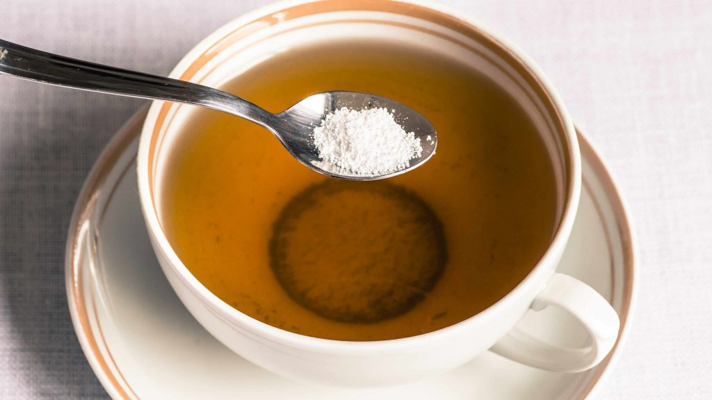 Se añade una cuchara de edulcorante artificial en una taza de té