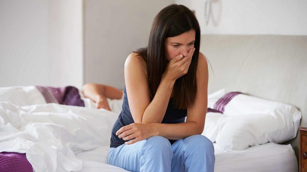 Mujer sentada al borde de la cama que se cubre la boca con la mano porque parece que tiene náuseas matutinas.