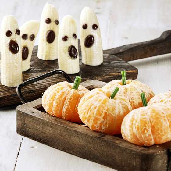 a wooden tray of healthy Halloween treats of bananas and tangerines
