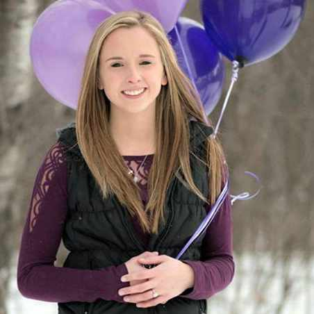 brain patient Nikki in the woods holding purple balloons