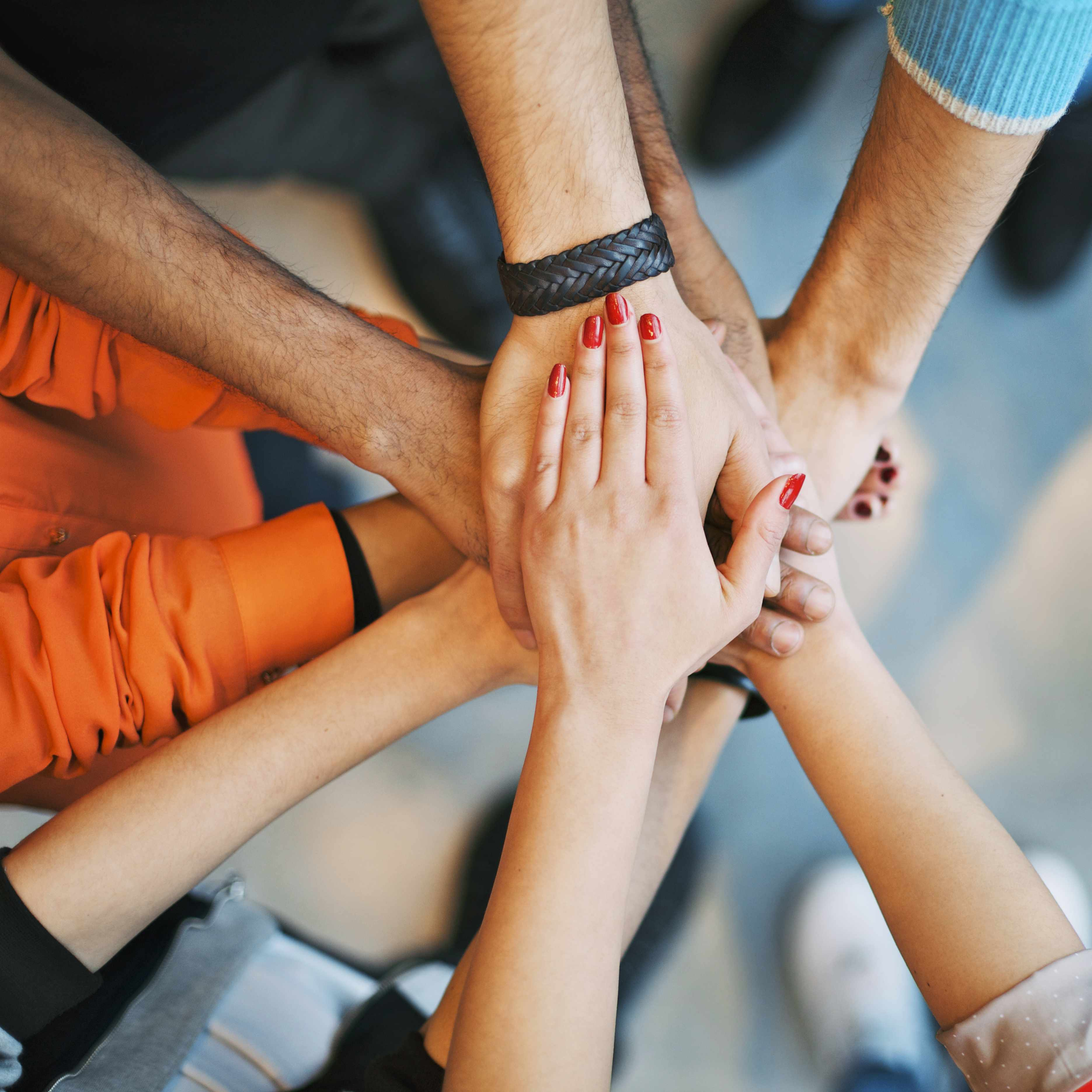 group of people stacking arms and hands on top of each other to show unity