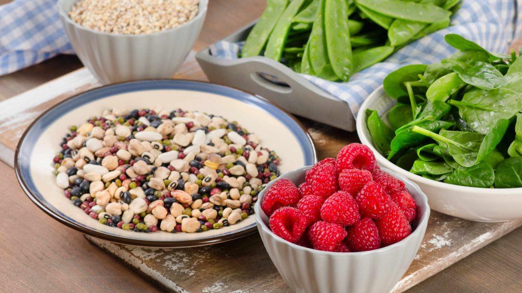 Alimentos con alto contenido de fibra, hojas de espinaca, frutos secos y bayas frente a un fondo de madera.