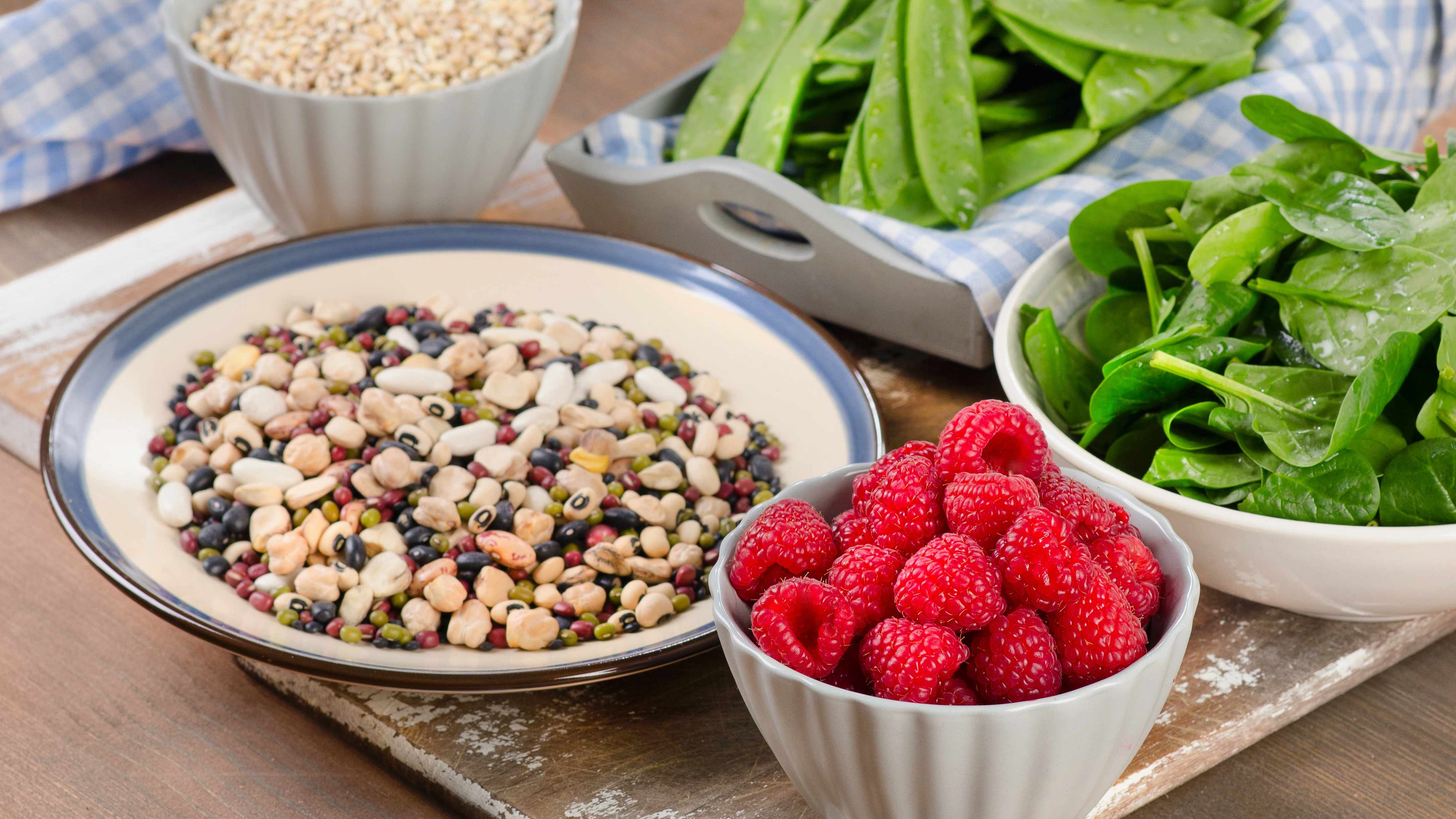 high fiber foods, spinach leaves, nuts and berries on a wood background