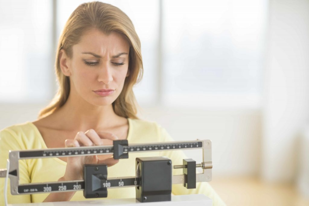 a woman on a weight scale looking disappointed