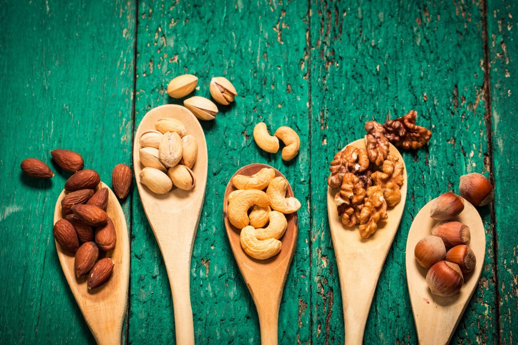 an assortment of nuts in wooden spoons, on a weathered green painted wooden table