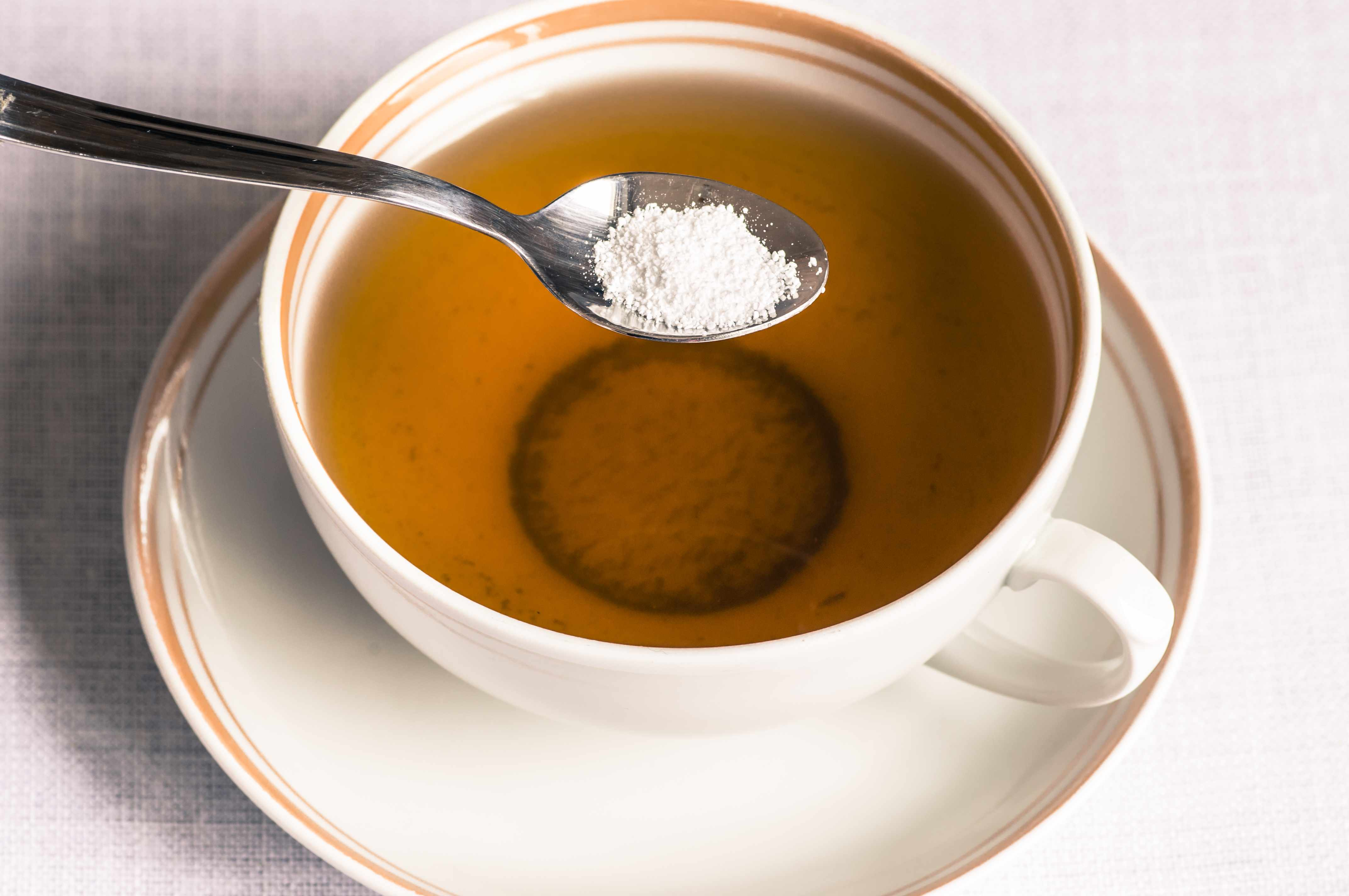 a spoonful of artificial sweetener being put in a cup of tea
