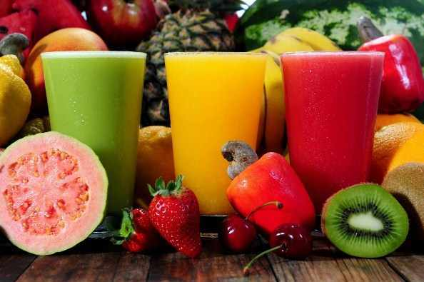 Various whole fruits and three glasses of juice smoothie