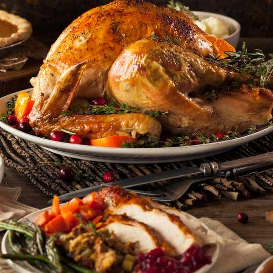 a Thanksgiving table filled with holiday foods, turkey, pumpkin pie, stuffing and geen beans