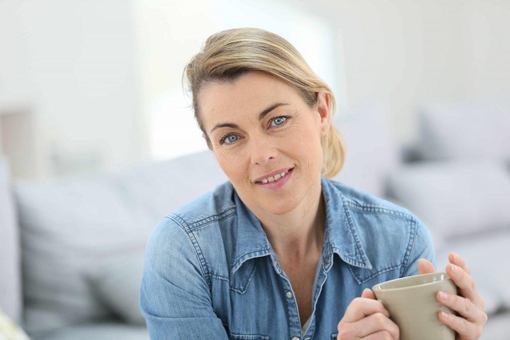 Mujer de mediana edad con una taza en sus manos