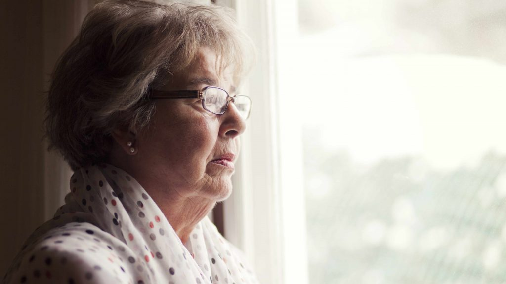 a profile close-up of a serious-looking older woman looking out a window