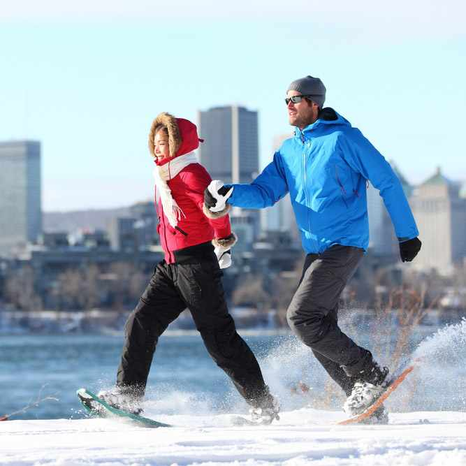 a smiling, warmly dressed couple snowshoeing along a river, with a city skyline in the background